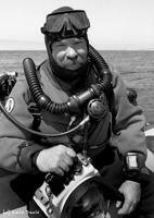 Underwater photographer, Chuck Davis  prepares for a dive beneath Monterey Bay, Monterey, CA.  Photograph taken by Chuck's son and dive partner, Cole Davis.